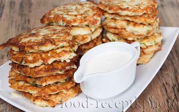 На фото горка оладий из кабачков на белой тарелке и белый соусник со сметаной