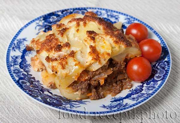 На фото Картофельная запеканка с мясным фаршем и помидорами черри в синей тарелке