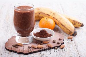 На фото в стакане смузи с мандарином,бананом и какао, бананы и мандарин на заднем плане, в маленькой миске порошок какао и рядом миндальные орехи