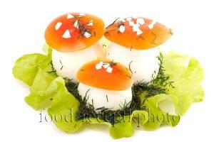 На фото фаршированные яйца в виде грибов мухоморов на листьях салата
