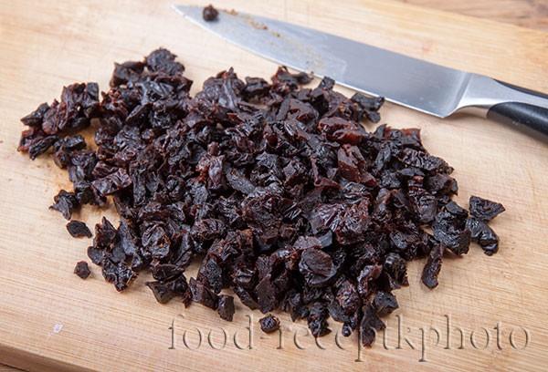На фото сушеный чернослив на разделочной доске нарезанный на мелкие части