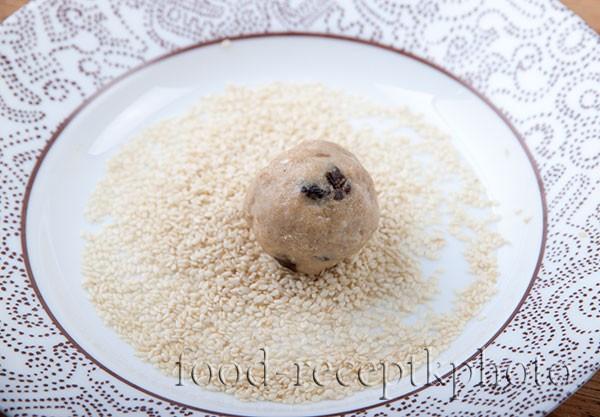Заготовки для печенья в виде шариков в тарелке с семенами кунжута