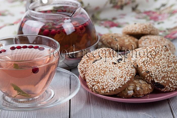 На фото печенье в тарелке и ягодно-травяной чай в стекляной прозрачной чашке и в стеклянном чайнике на заднем плане