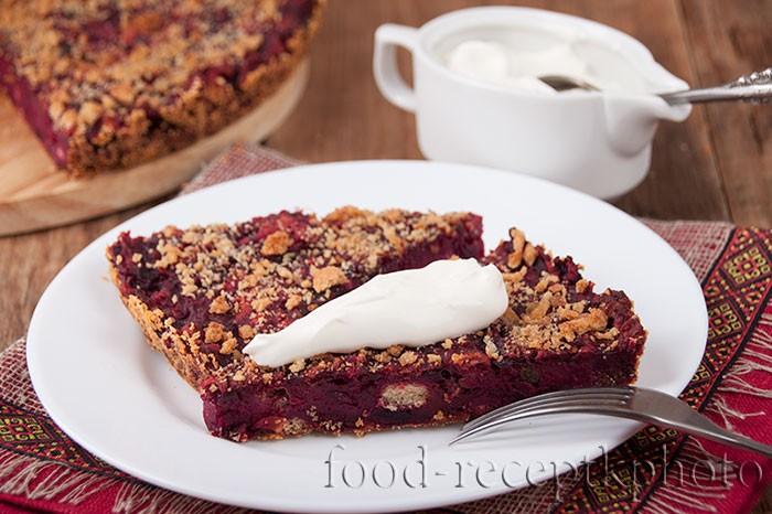 На фото два кусочка свекольного пирога в белой тарелке, белый соусник со сметаной на деревянном столе