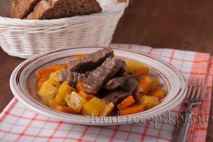 На фото тушеное мясо с овощами репы и моркови в тарелке, которая стоит на клетчатой салфетке и на заднем плане белая хлебница с черным хлебом