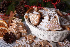 На фото имбирное новогоднее печенье украшенное глазурью и с новогодней декорацией