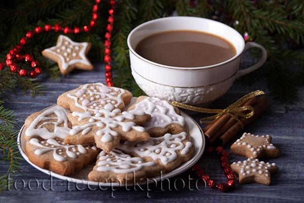 На фото имбирное печенье в белой тарелке и какао в белой чашке на фоне еловых ветвей