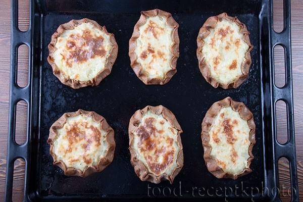 На фото готовые калитки с картофелем на противне