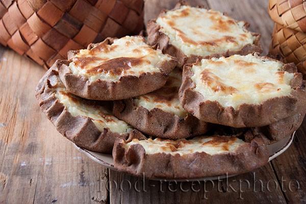 Калитки картофельные архангельские в тарелке на старом деревянном столе и на заднем плане берестяной туес
