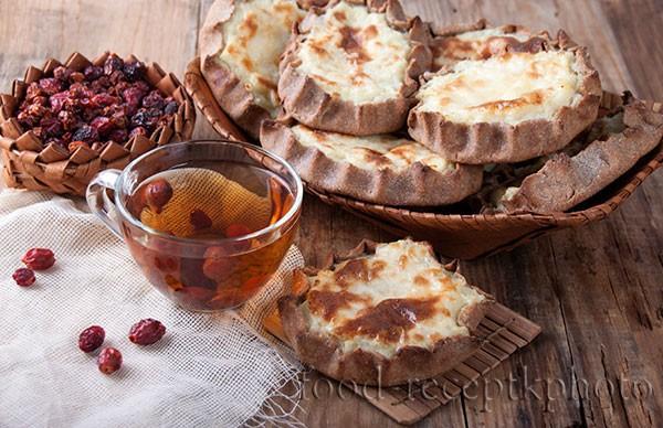 На старом деревянном столе калитки с картофельной начинкой в берестяной тарелке и рядом чай из шиповника в стеклянной чашке и сухой шиповник в берестяной коробке