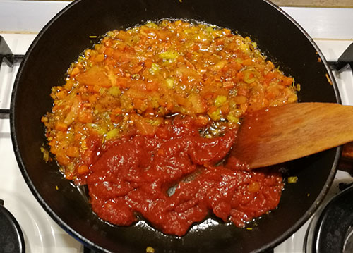 На фото в сковороде обжаривается репчатый лук,морковь,помидор и чеснок с томатной пастой
