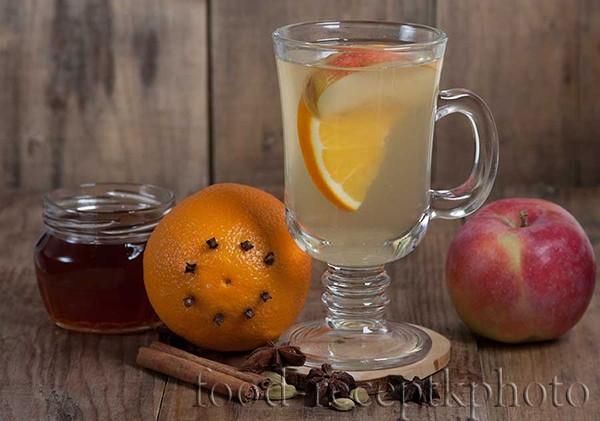 На фото на старом деревянном столе в бокале для глинтвейна фруктовый чай из яблок и апельсина,рядом яблоко,апельсин и баночка с медом .