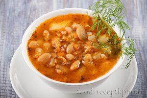 На фото в белой миске суп из белой фасоли украшенный веточкой укропа
