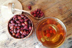 На фото сухой шиповник в берестяном туесе и чай из шиповника в стеклянной кружке
