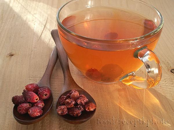 На фото в стеклянной чашке чай из шиповника и рябины, рядом с чашкой в деревянных ложках сухой шиповник и сухая рябина