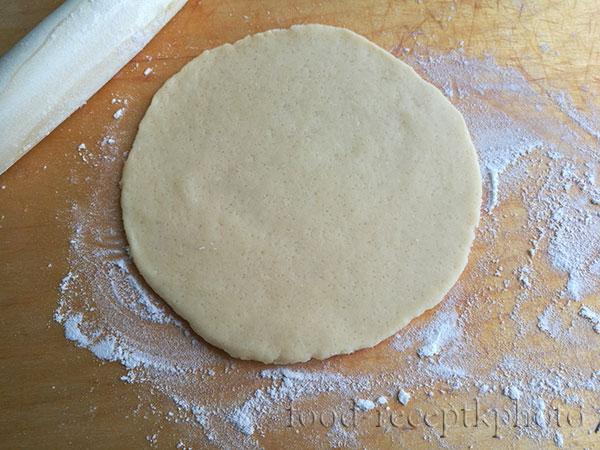 На фото на разделочной доске раскатанное в круг тесто