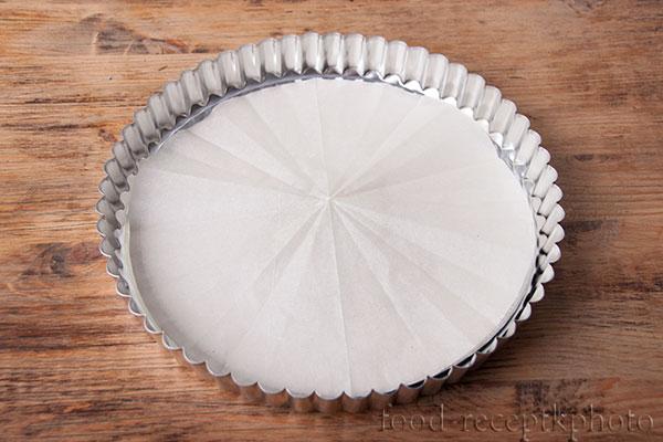 На фото железная форма для выпечки застеленная пекарской бумагой