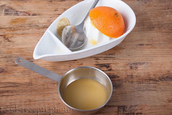 На фото в железной кокотнице смесь сахара и апельсинового сока для приготовления сиропа