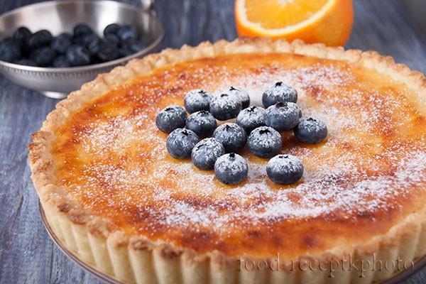 На фото творожный пирог с ягодами голубики обсыпанный сахарной пудрой