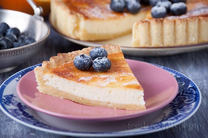 На фото кусок творожного пирога на розовой тарелке и на заднем плане большой пирог и ягоды голубики
