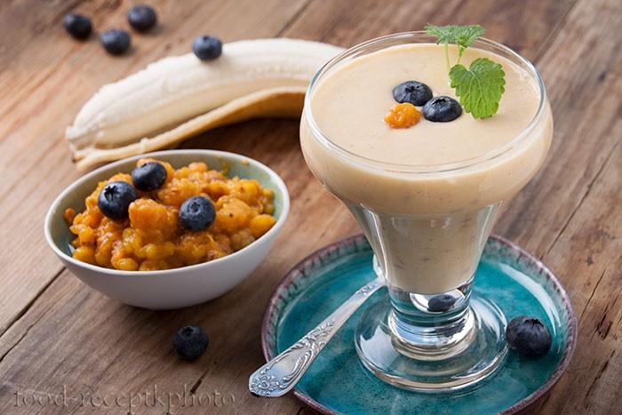 На фото бокал со смузи из морошки с бананом ,украшенный ягодами голубики на старом деревянном столе