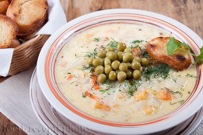 На фото в тарелке овощной суп с зеленым горошком и гренками