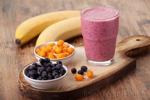 На фото Облепихово-черничный смузи в стакане на разделочной деревянной доске, и рядом в маленьких салатниках ягоды замороженной облепихи и черники и бананы на заднем плане.