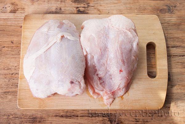 На фото на разделочной доске сырые куриные грудки
