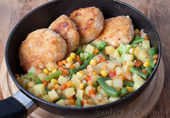 На фото куриные котлеты с овощной смесью в сковороде