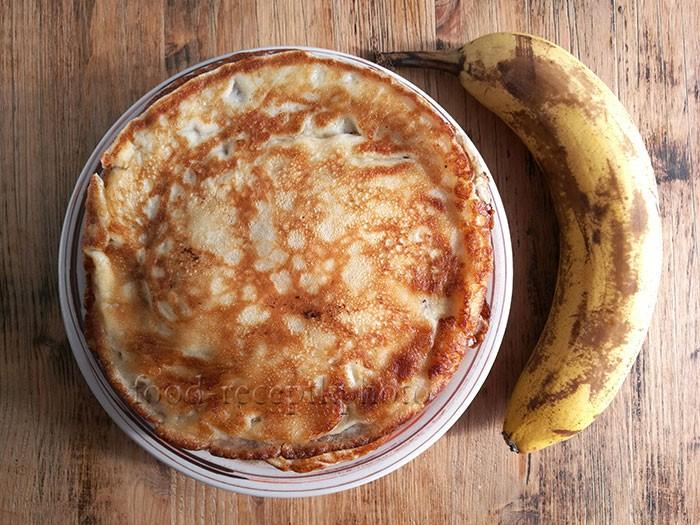 На фото готовые блины в тарелке на деревянном столе и рядом банан
