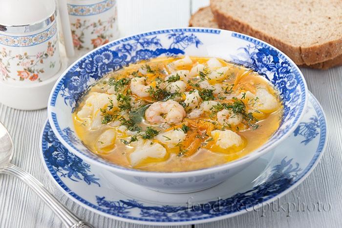 На фото Суп из цветной капусты с креветками в синей тарелке на белом деревянном столе