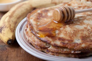 На фото в тарелке блины политые медом и рядом находится банан