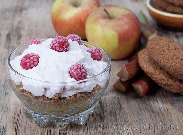 На фото стеклянная креманка с десерттом из ревеня,яблок,творога и печенья