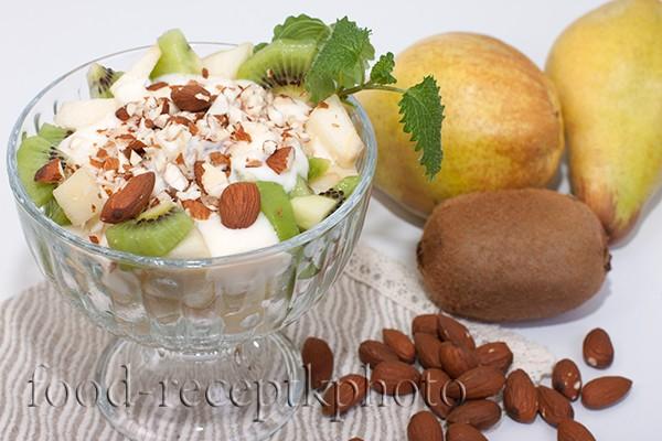 На фото Фруктовый салат с грушей и киви в стеклянном салатнике
