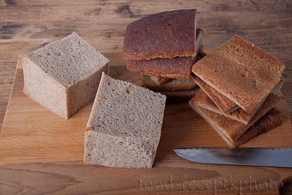 На фото буханка черного хлеба на разделочной доске разрезанная на час