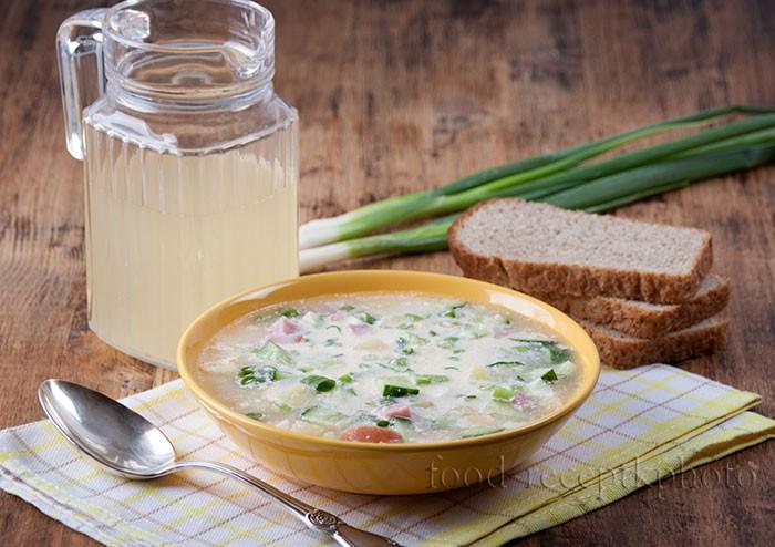 На фото в желтой тарелке окрошка и рядом кувшин с квасом,черный хлеб и зеленый лук