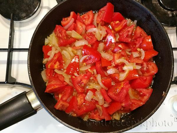 На фото в сковороде жарится лук и помидоры