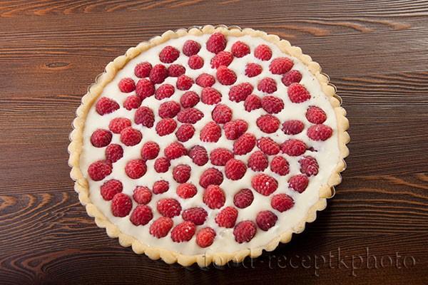 На фото форма для выпечки с песочным тестом и сметанной заливкой с ягодами малины для пирога