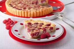 На фото в тарелке кусок пирога с малиной и на заднем плане пирог с малиной