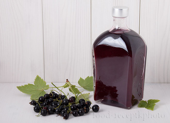 На фото бутылка с соком черной смородины и ягоды смородины рядом с бутылкой на белом деревянном столе на фоне белой деревянной стены