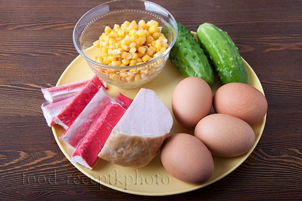 На фото ингредиенты для приготовления салата  из крабовых палочек с мясом,яйцами,кукурузой и свежими огурцами