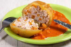 На фото в зеленой тарелке фаршированный болгарский перец с соусом