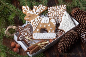 На фото в подарочной коробке пряники-козули на фоне еловых веток и еловых шишек