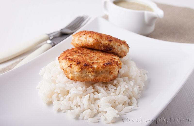 На фото в белой тарелке рыбные котлеты с гарниром из риса и соусник с рыбным соусом рядом на заднем плане