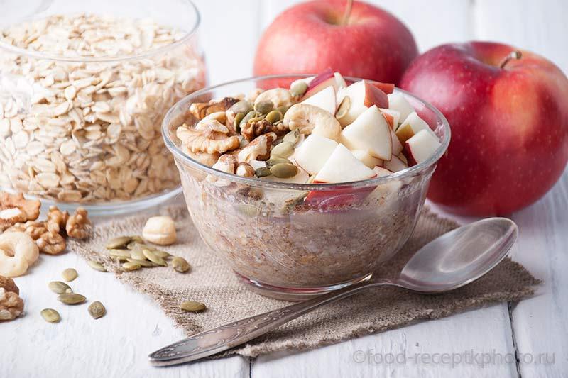 Бирхер мюсли с использованием овсяных хлопьев , тертого яблока, лимонного сока,грецких орехов ,миндаля и кешью и украшенными кусочками свежего яблока.