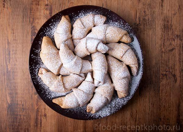 Домашние рогалики с сахарной пудрой в круглой коричневой тарелке на деревянном столе