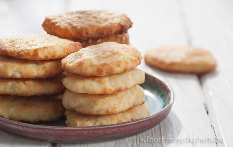 Творожное печенье в бирюзовой тарелке на белом деревянном столе