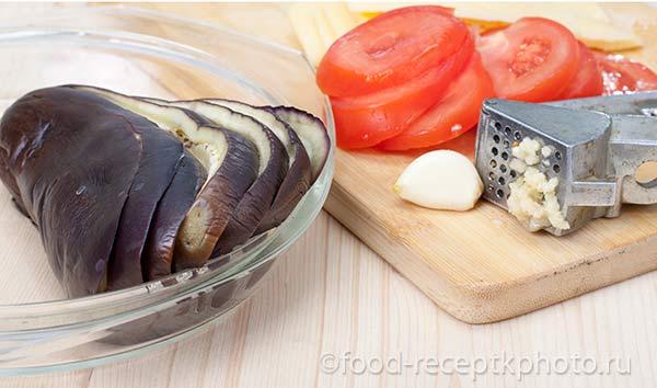 Ингредиенты для запеченных баклажан: помидор,чеснок,сыр,баклажан на разделочной доске