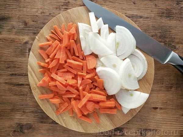 Морковь и репчатый лук на разделочной доске