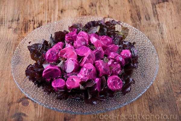 Отварная свекла с листьями салата и со сметаной в стеклянной тарелке